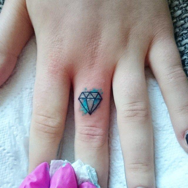 small colored diamond tattoo on finger