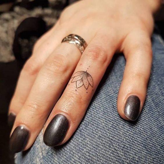 small fineline lotus flower tattoo on finger