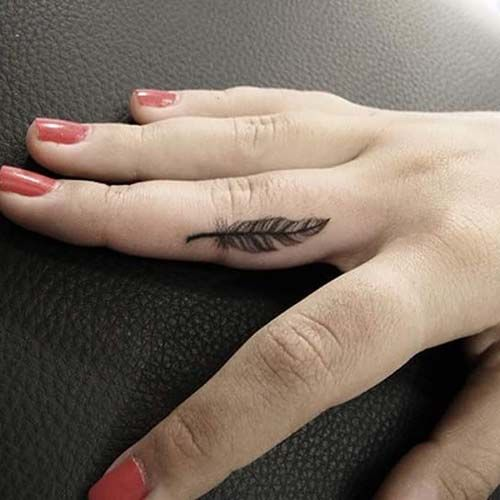 small feather finger tattoo on middle finger