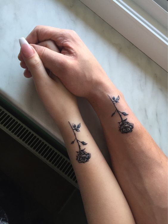 couples tattoo on wrist with small roses