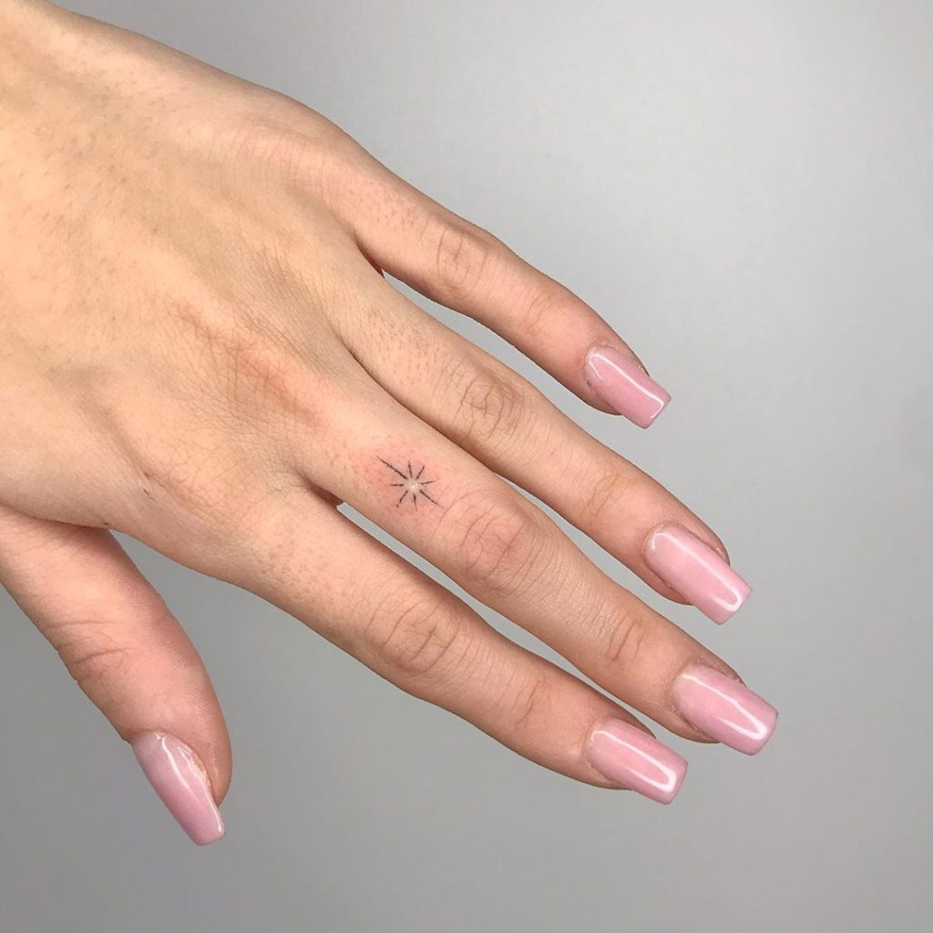 mini star tattoo on finger